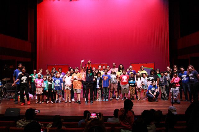 group of Chicago elementary school students on stage with Barrel of Monkeys teachers at the University of Chicago