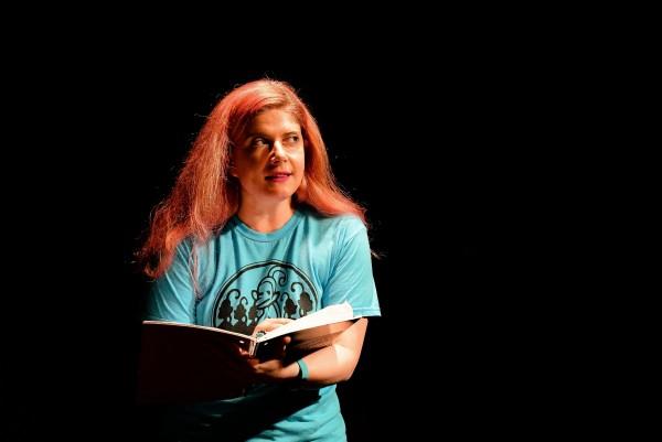 Rachel Wilson against a black background holding a notebook