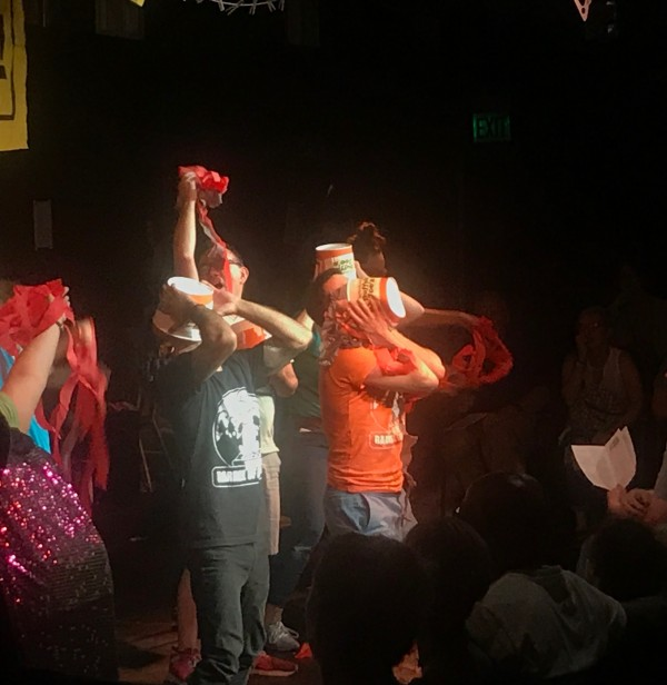 Barrel of Monkeys ensemble members putting Buffalo Joes buckets on their head during a performance of That's Weird, Grandma