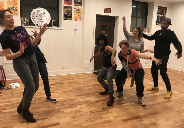 Barrel of Monkeys cast members acting as cats during a rehearsal in Uptown