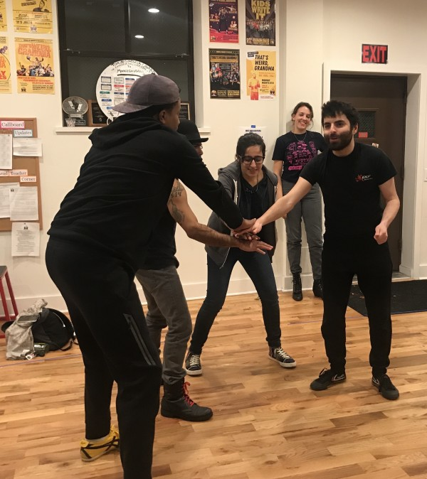 Four Barrel of Monkeys cast members putting their hands in together at the start of a sketch about lacrosse during a rehearsal in Uptown