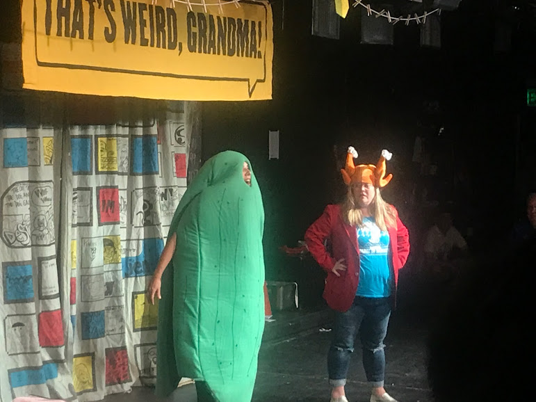 Jen Johnson in a chicken hat and Ida Cuttler in a pickle costume performing KFP during That's Weird, Grandma: Stories About Food